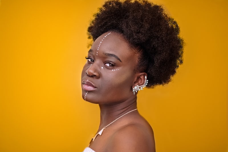 Black woman with natural hair and painted face in front of a gold wall | wellness trends 2020